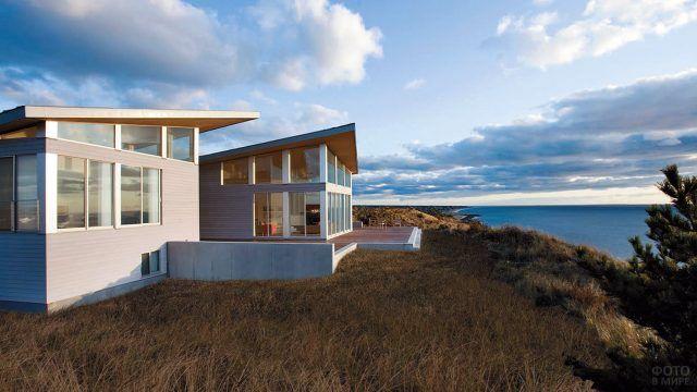Современный дом с панорамным остеклением на высоком морском берегу