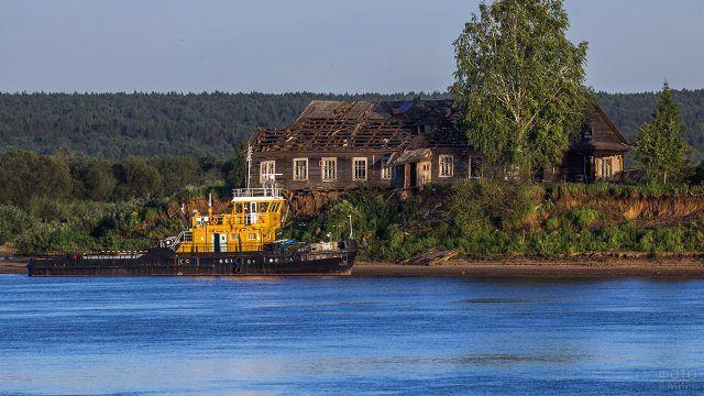 Старинный деревянный дом и корабль на реке в деревне Коромыслово