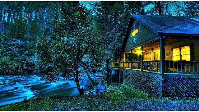 Вечерние огни на веранде деревянного дома в лесу на берегу стремительной речки
