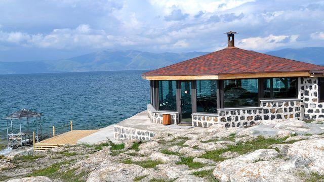Здание кафе с панорамным остеклением и черепичной крышей на берегу моря