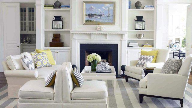 Белая мебель в светлой каминной зоне гостиной у белого камина