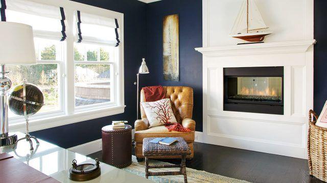 Белый камин на фоне тёмно-синей стены в уютной комнате с креслом у окна