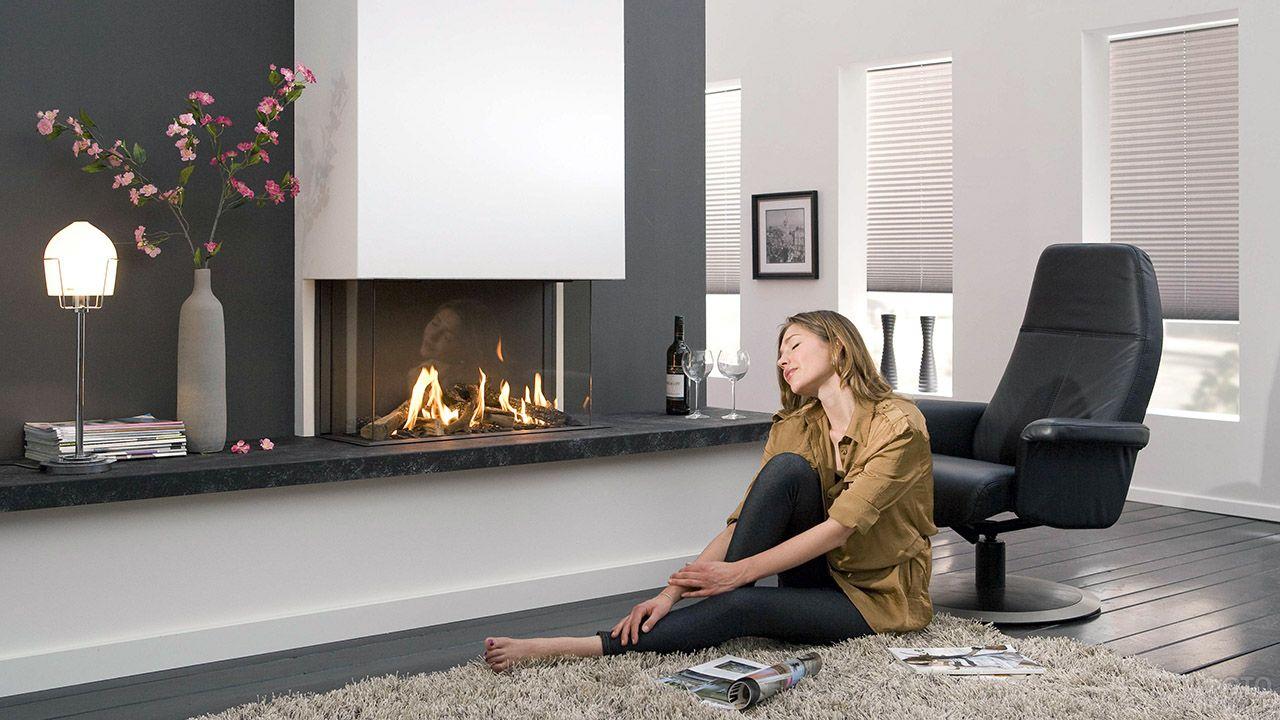 Девушка на ковре перед камином в современной квартире