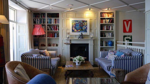 Камин в классической гостиной с полосатыми диванами