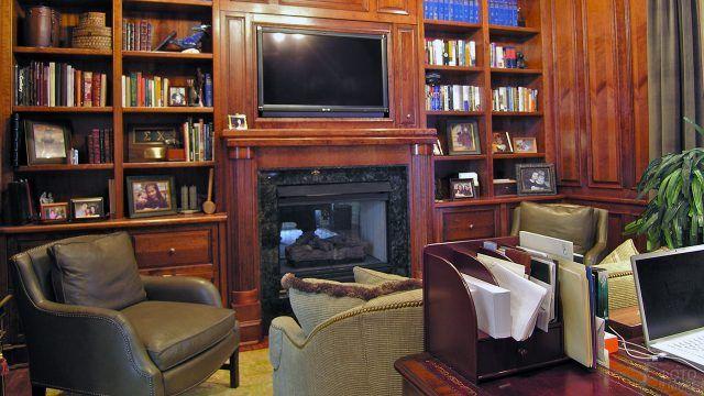 Классический кабинет с библиотекой и креслами у камина
