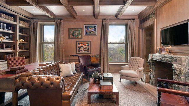 Классический кабинет с кожаной мебелью и мраморной отделкой камина под плазмой