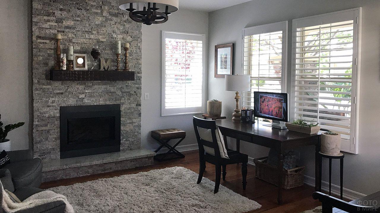 Трендовая серая комната с каменным фасадом камина и рабочим столом у окна