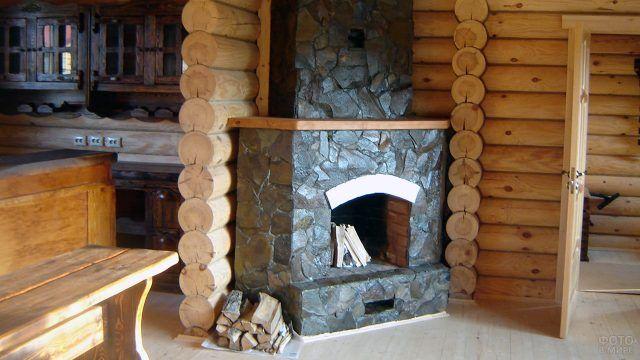 Угловой камин с каменной облицовкой в бревенчатом доме