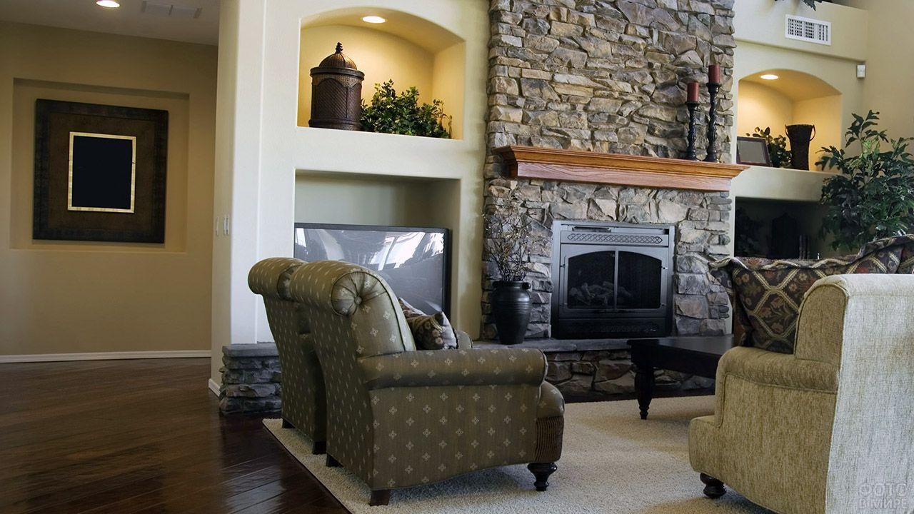 Уютный интерьер гостиной с камином отделанным природным камнем