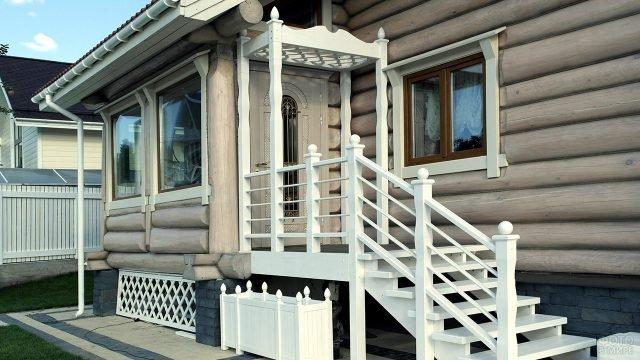 Бревенчатый дом с деревянным белым крылечком с навесом