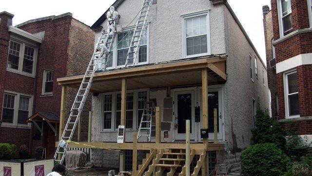 Деревянный навес над деревянным крыльцом в процессе отделки фасада частного дома