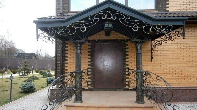 Кованый козырёк с орнаментом в стиле модерн над крыльцом кирпичного дома