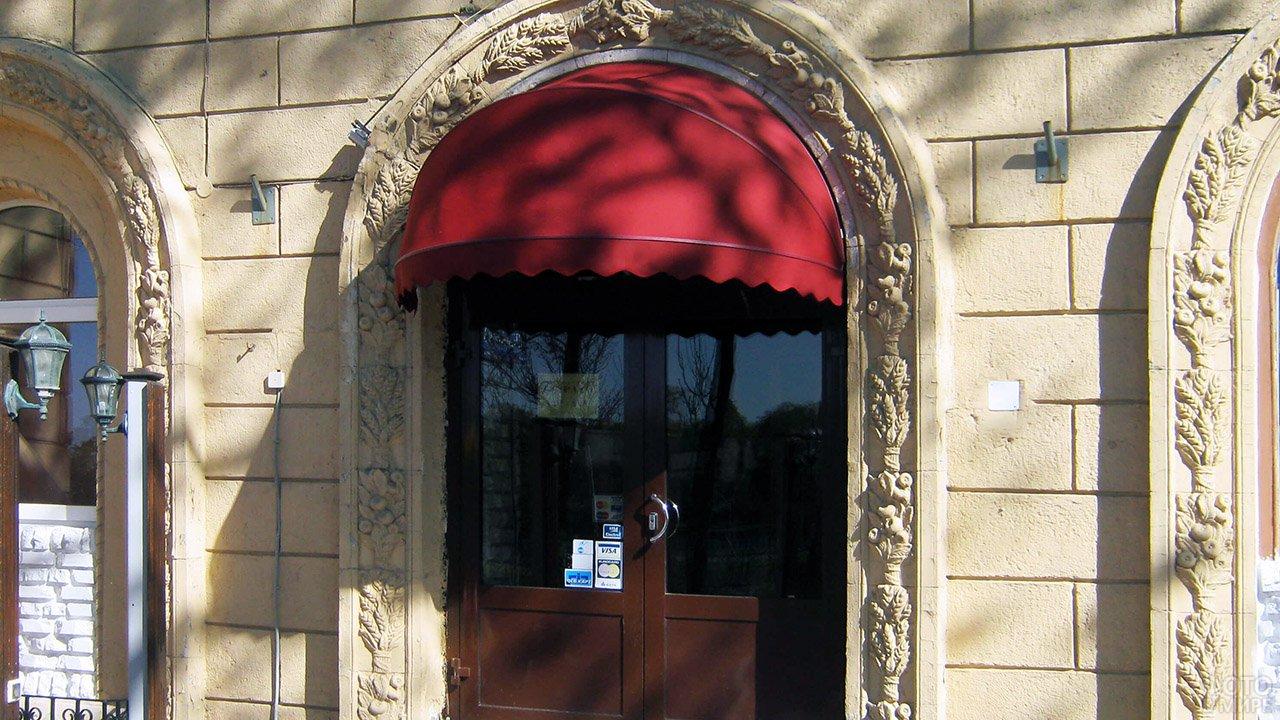 Красная корзинная маркиза над крылечком бокового входа старинного здания