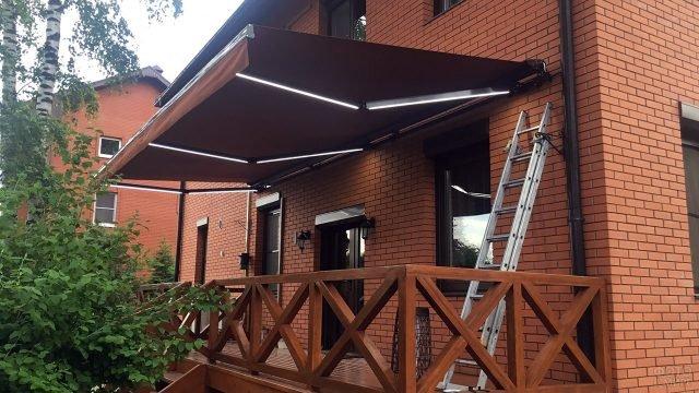Маркиза полузакрытого типа со встроенным светодиодным освещением над деревянным крыльцом загородного дома