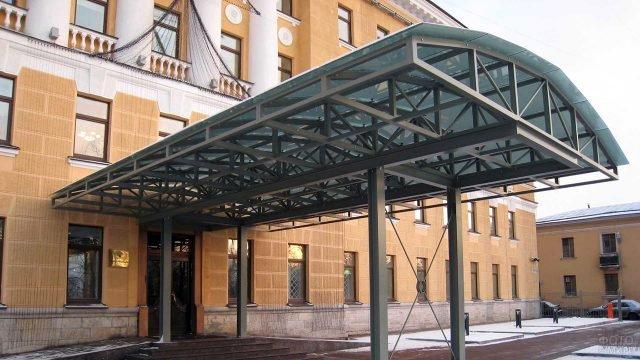 Массивный длиный козырёк над крыльцом офисного здания