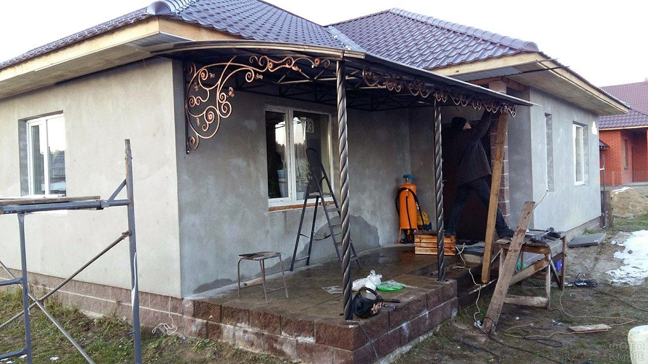 Монтаж кованого козырька над широким крыльцом садового домика