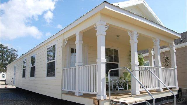 Навес над крыльцом с колоннами дома-фургона с ванильным сайдингом на фасадах