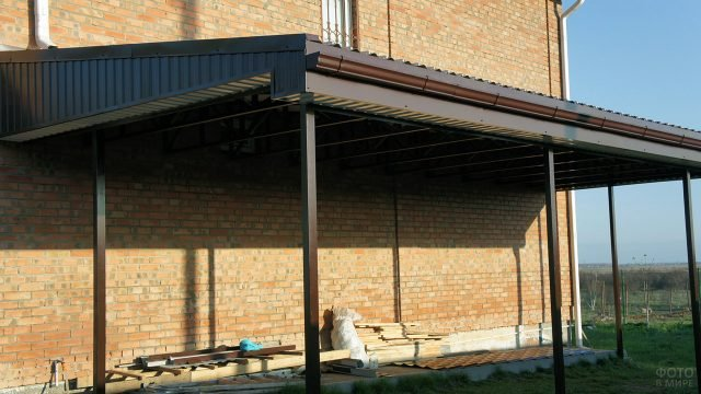 Навес над открытой верандой у кирпичного фасада загородного дома
