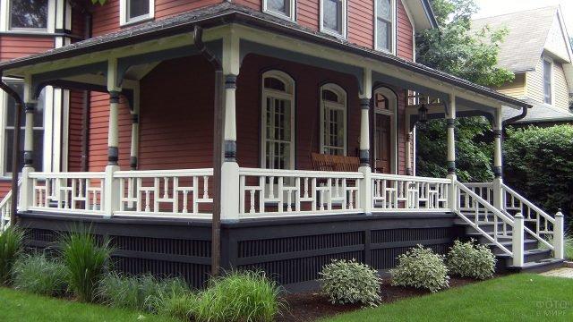 Навес над угловой верандой с белыми деревянными колоннами и перилами
