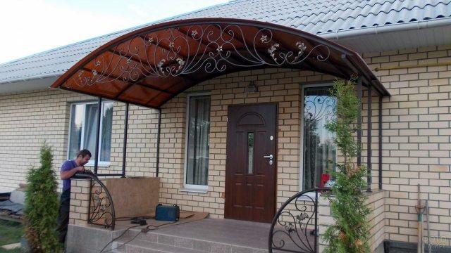 Округлый кованый козырёк загородного дома с узором из виноградной лозы