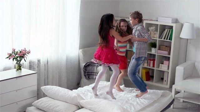Дети прыгают на кровати в светлой детской спальне с книжным стеллажом и креслами