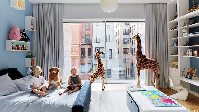Дети с собакой на кровати в спальне с игровой зоной и жирафами у окна
