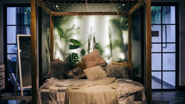 Дизайнерский интерьер спальни с мохнатыми подушками на фоне стеклянной стены тропического сада