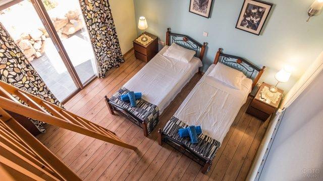 Лаконичная гостевая спальня с пёстрыми шторами и дощатым полом