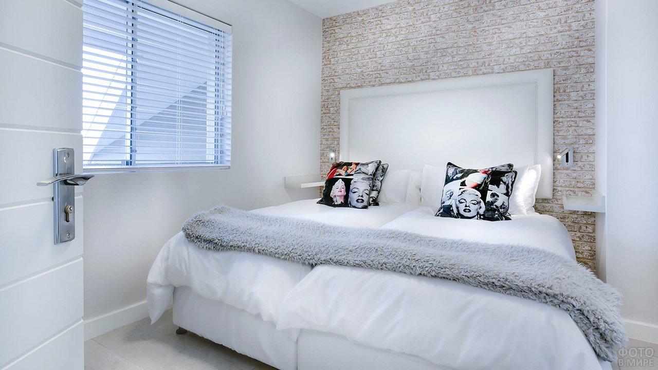 Маленькая белая спальня в стиле лофт с контрастными пёстрыми подушками
