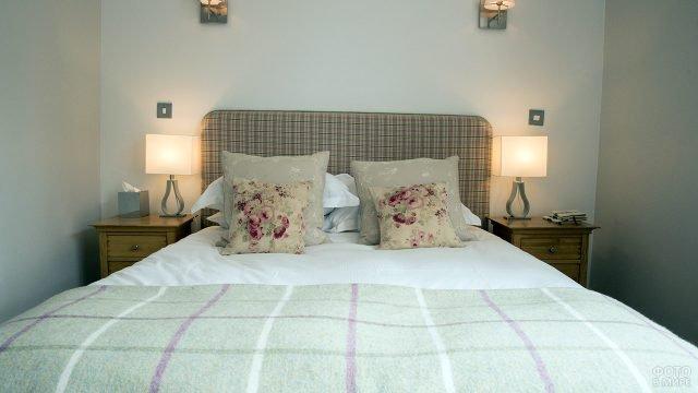 Маленькая светло-бежевая спальня с декоративными подушками в стиле прованс на двуспальной кровати