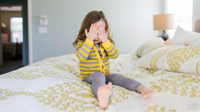 Малышка закрыла глаза ладошками сидя на кровати в просторной светлой спальне
