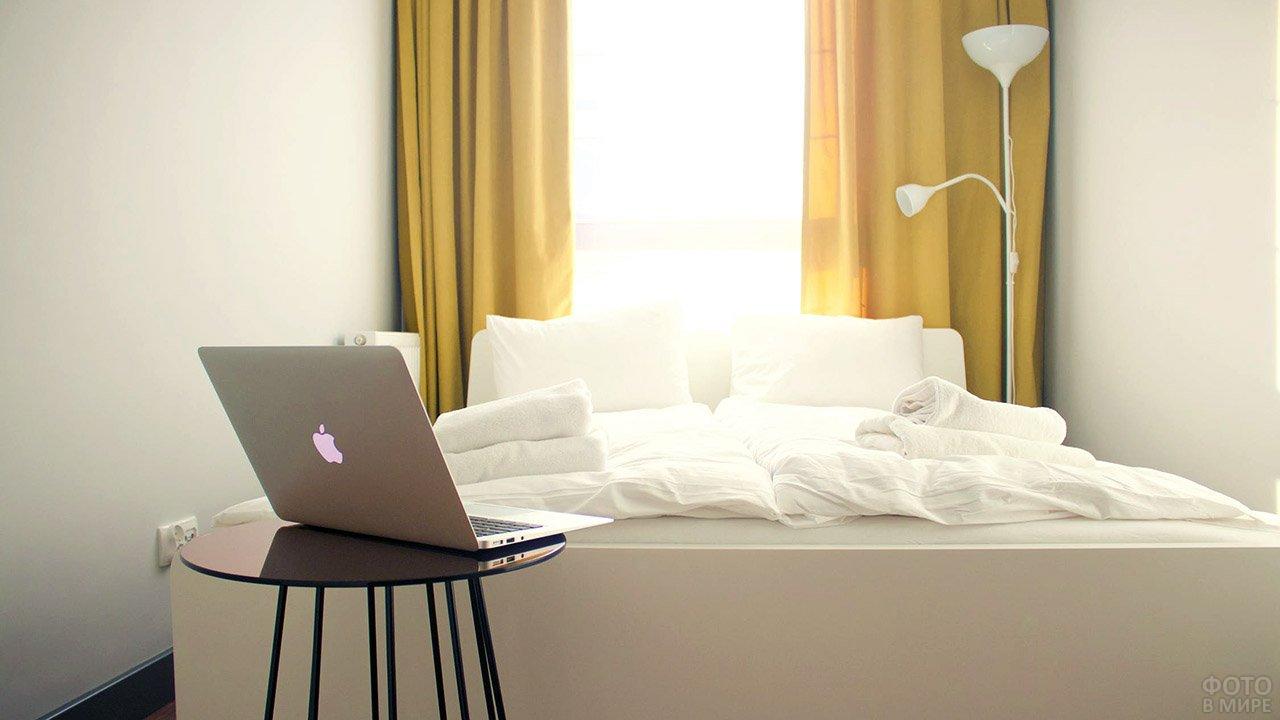 Ноутбук Apple в светлой спальне городской квартиры