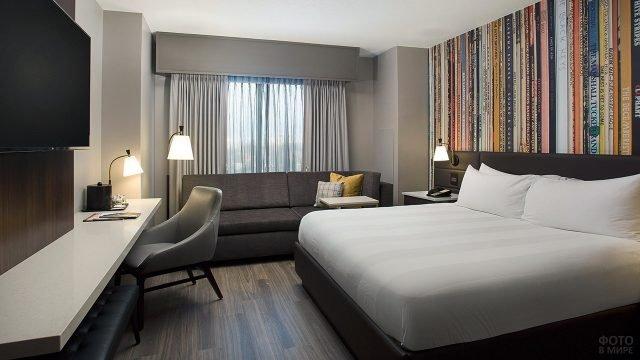 Спальня с просторной кроватью у пёстрой стены туалетным столиком и диваном у окна