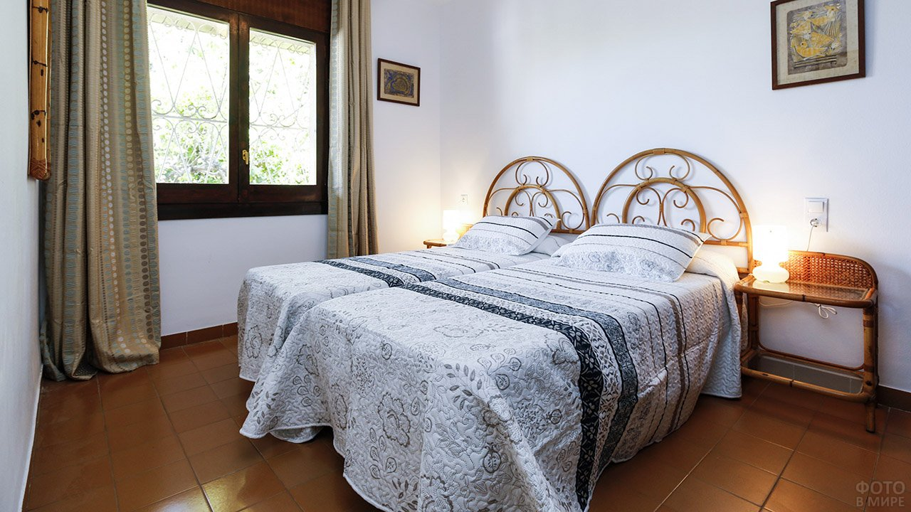 Светлая гостевая спальня кроватями с ажурным изголовьем и контрастным текстилем