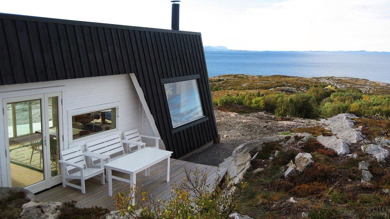 Чёрные стены и белая веранда загородного дома на высоком морском берегу
