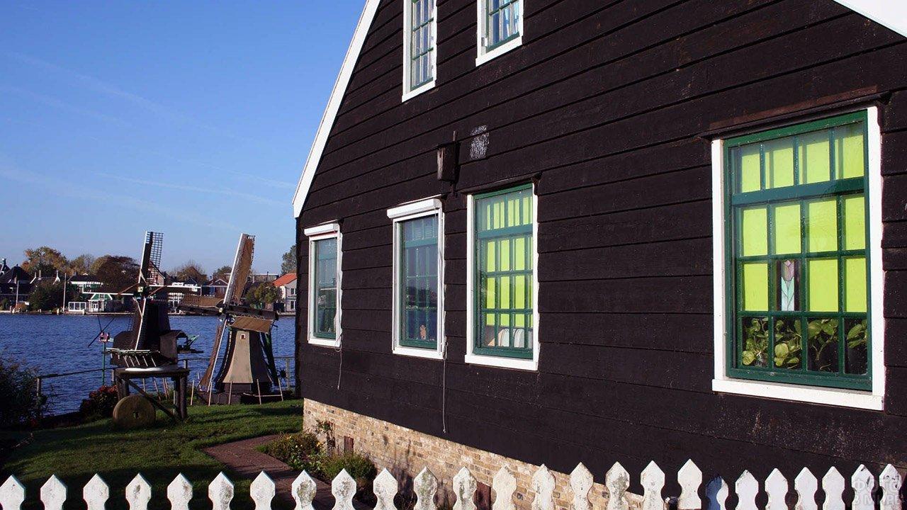 Чёрный деревянный дом с бело-зелёными рамами и декоративными мельницами на лужайке у озера