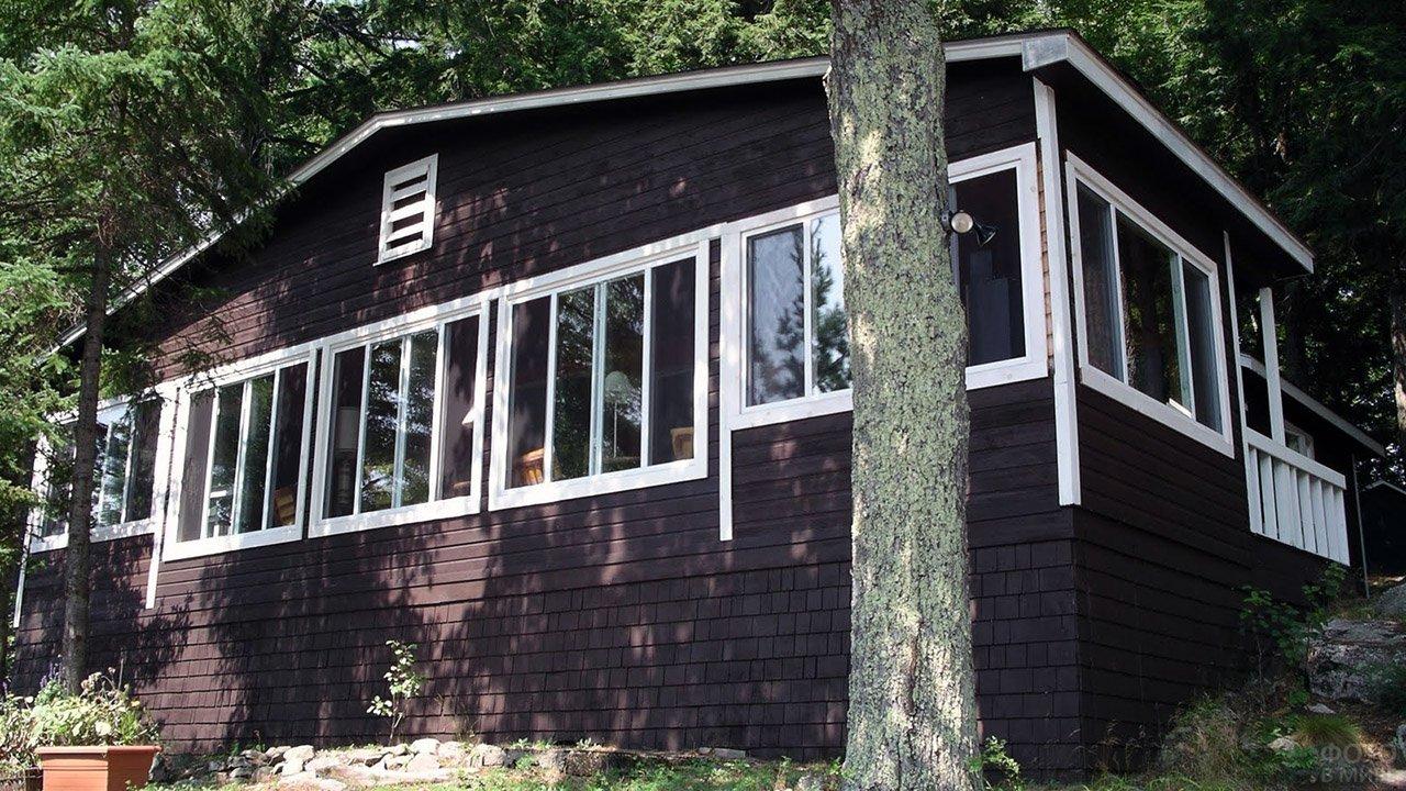 Чёрный фасад с белыми рамами деревянного дома на кирпичном подклёте