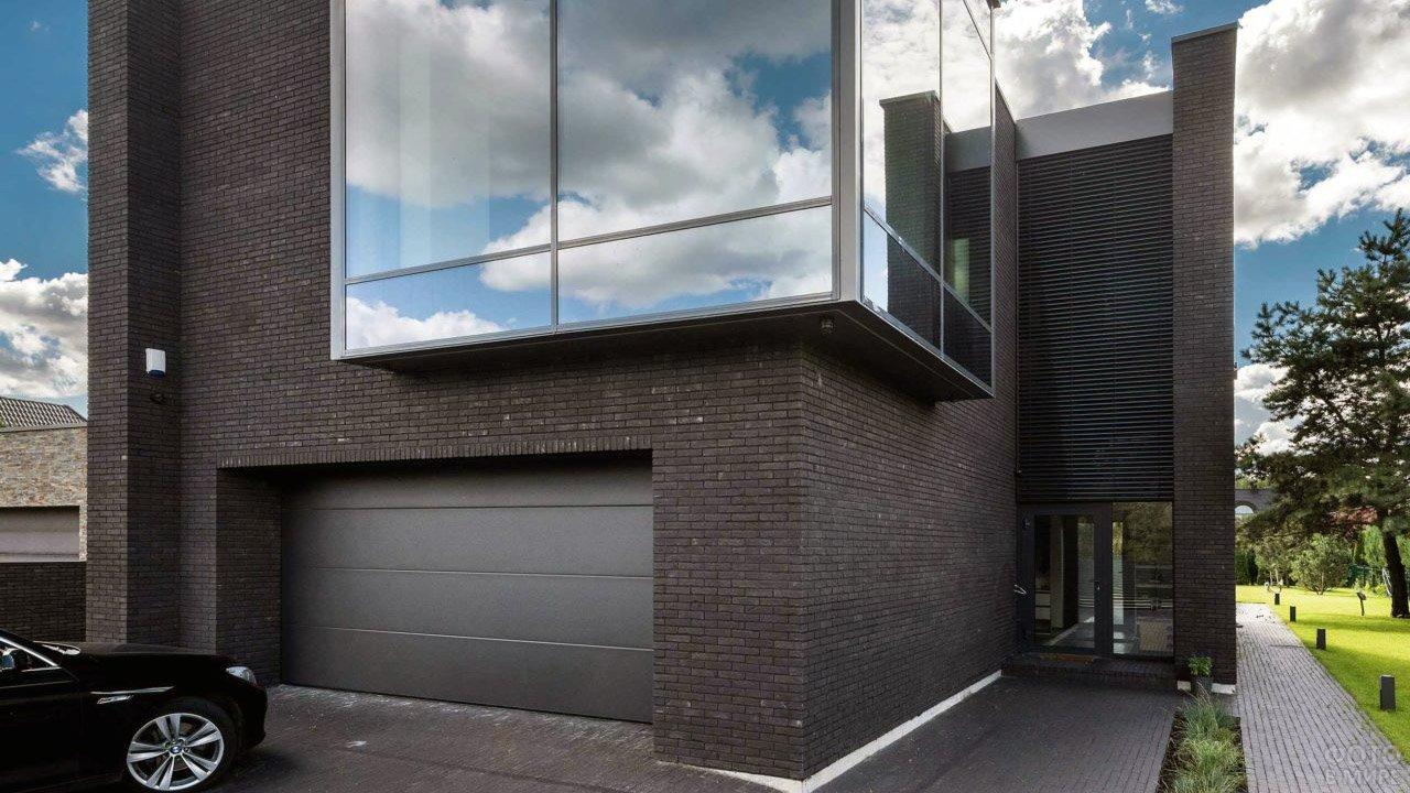 Чёрный кирпичный фасад частного дома с гаржом и панорамным остеклением веранды