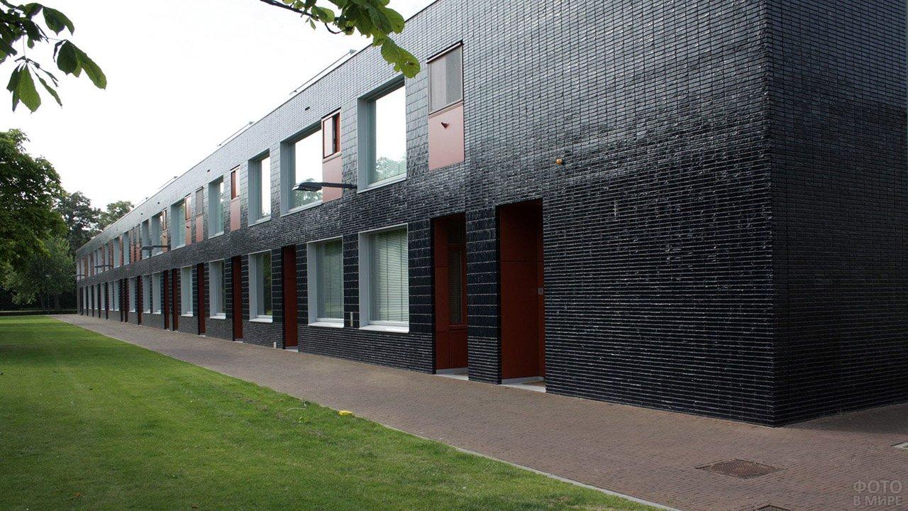 Чёрный облицовочный кирпич на фасаде многоподъездного дома