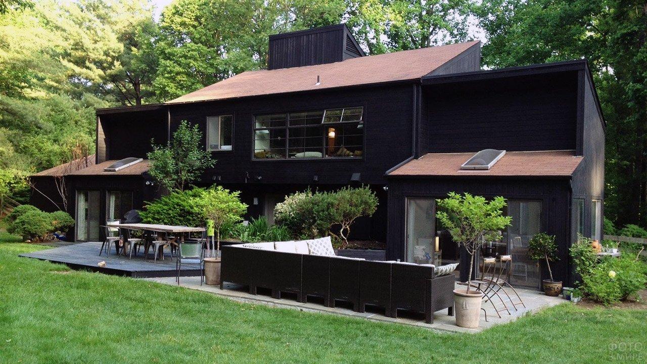 Чёрный загородный дом на зелёной лужайке под большими деревьями