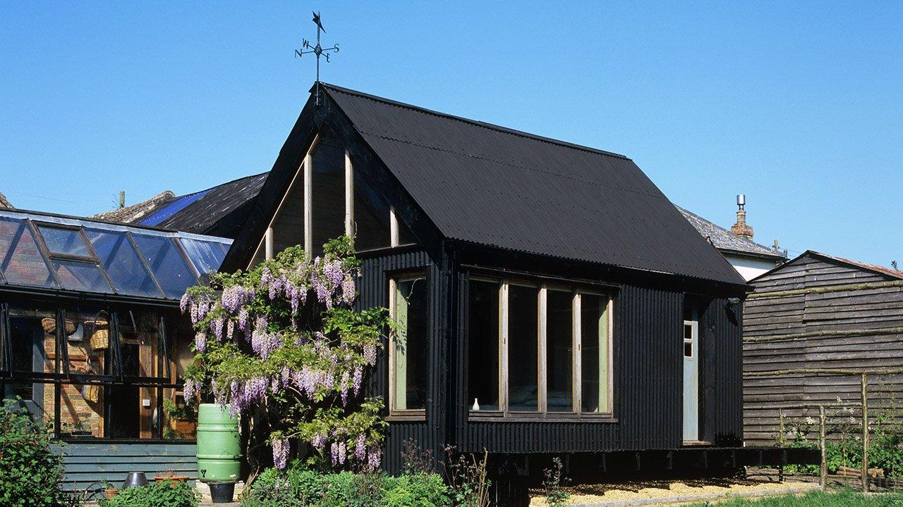 Дачный домик чёрного цвета на солнечном участке с цветущим деревом