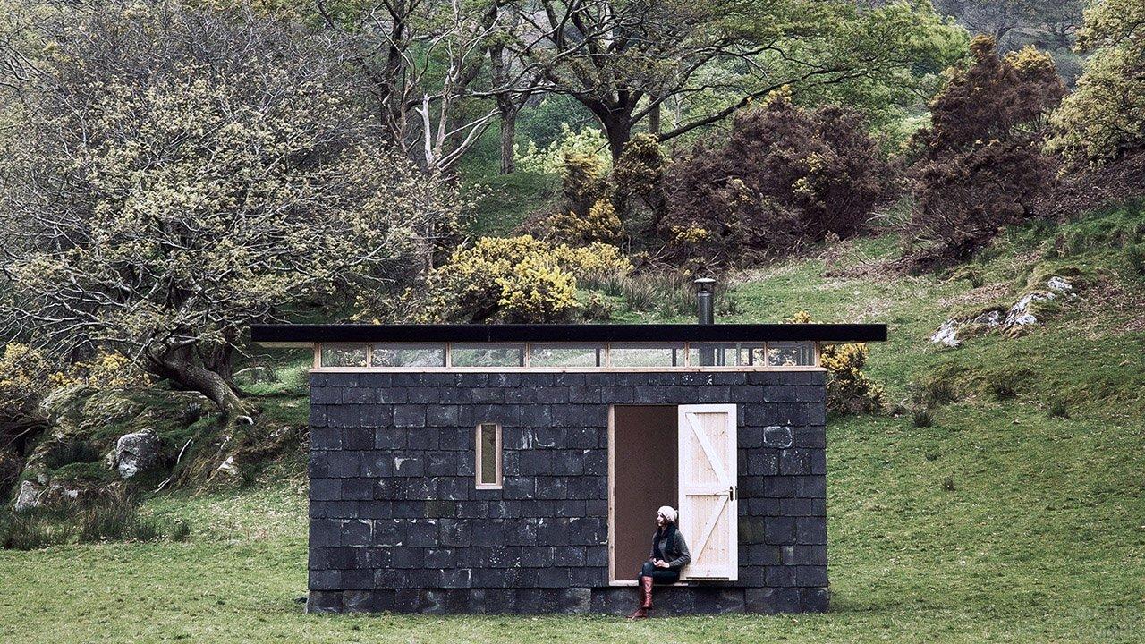 Девушка сидит на пороге маленького лесного домика из блоков чёрного цвета