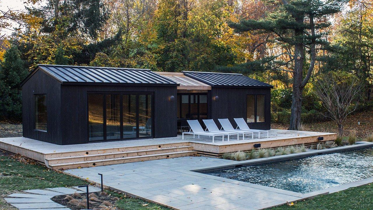 Небольшой загородный дом чёрного цвета с белыми шезлонгами у бассейна среди деревьев