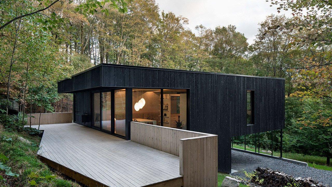 Уединённый чёрный дом на сваях со светлой открытой верандой среди деревьев