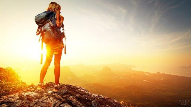 Альпинистка в лучах заката над осенней долиной