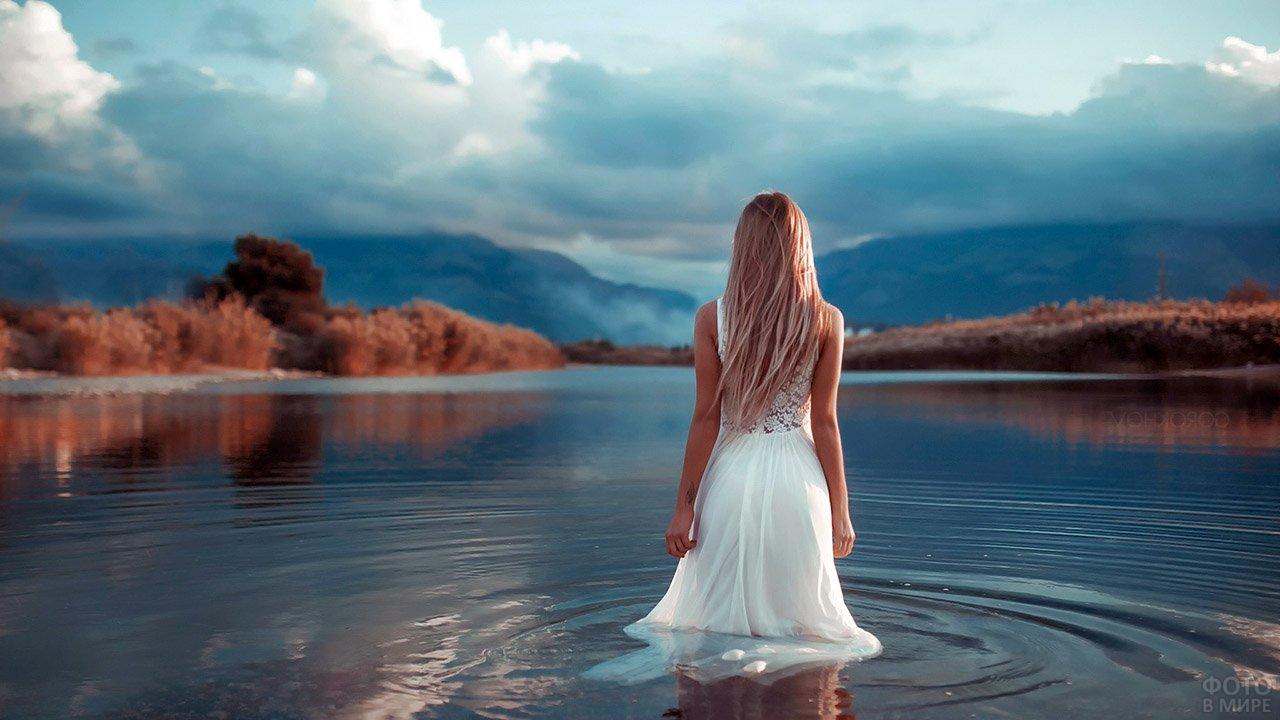 Блондинка в белом платье в воде лесного озера ранней осенью