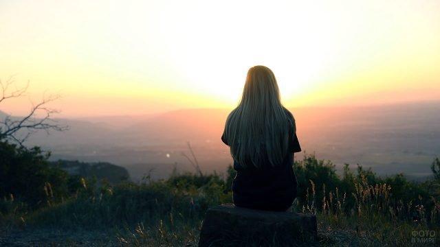 Блондинка в чёрном смотрит на восход над осенней долиной