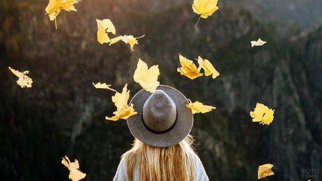 Блондинка в шляпе под листопадом на вершине горы