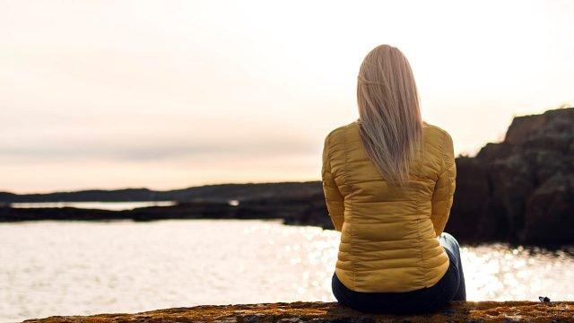 Блондинка в жёлтой куртке сидит у кромки моря