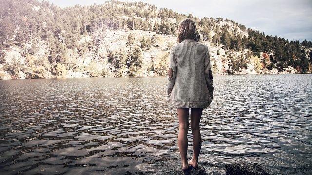 Босая светловолосая девушка в вязаном кардигане на мелководье гоного озера ранней осенью